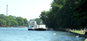 Ein blauer See auf dem zwei Schwäne schwimmen. Am Ufer sind zwei große Boote festgemacht. Das Ufer ist durch eine Mauer leicht erhöht und besteht aus grünem, kurzgeschnittenem Gras. Darauf liegen und sitzen Menschen in verschiedenfarbiger Badekleidung.