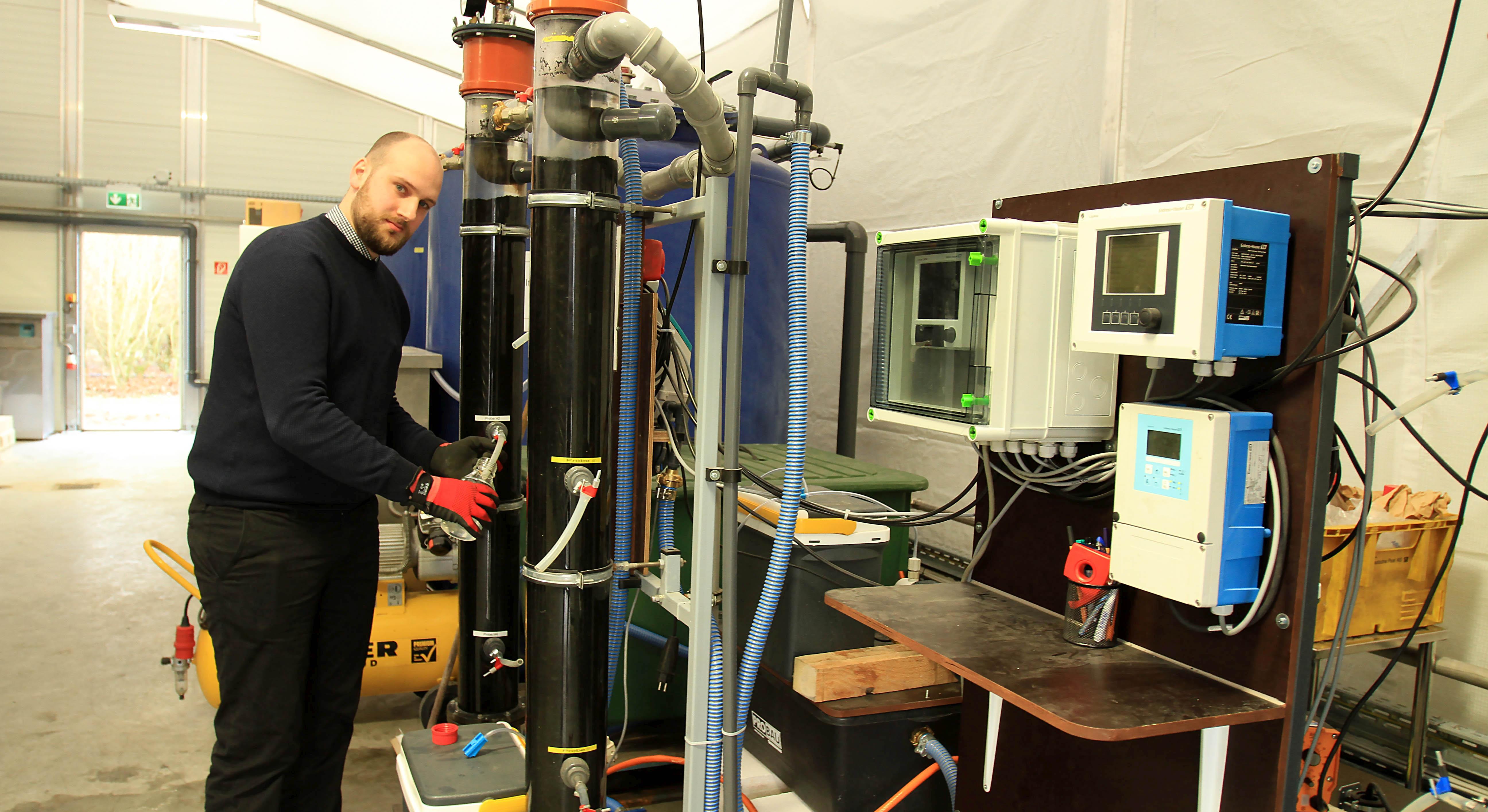 Thomas Fundneider von der TU Darmstadt entnimmt in der Halle mit der Versuchsanlage eine Wasserprobe. Foto: Sorger/Abwasserverband